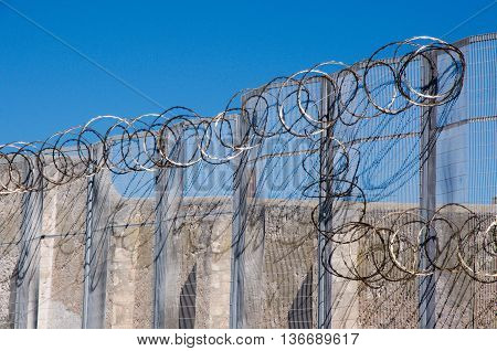 FREMANTLE,WA,AUSTRALIA-JUNE 1,2016:  Fremantle Prison detail of the sharp razor wire fencing with the limestone walls in Fremantle, Western Australia.