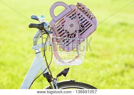 Womans hand bag in bicycle basket sloseup