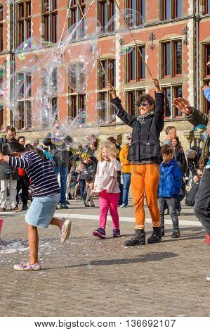 Amsterdam - September 18, 2015: Woman Making Huge Bubble Balloons Outdoors