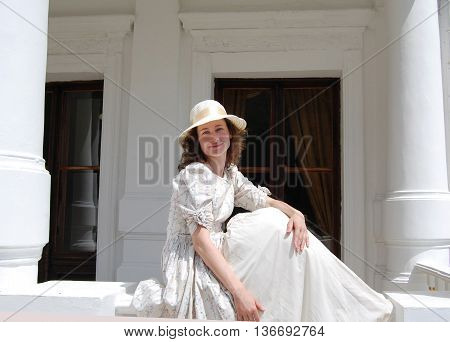 European woman sitting in sunshine and touching hair in vintage dress near palace. White color, curly hair, sensitive, sensuality.