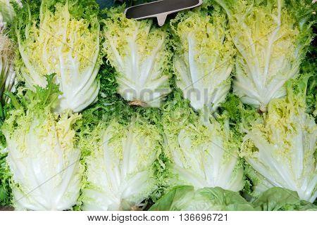 Green bundles of lettuce frieze for sale at a market