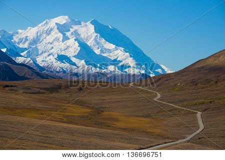 Mount McKinley's snowy peak with the park road and tundra in the foreground, Denali National Park, Alaska, US