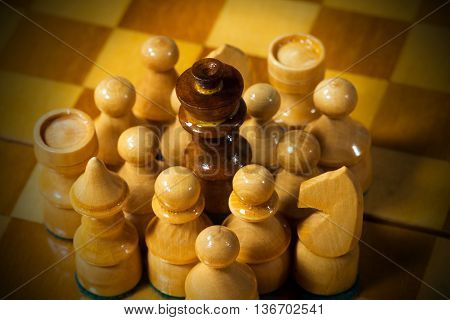 Detail of wooden black chess king surrounded by white pieces pawns tower queen horse bishop on a wooden chess board