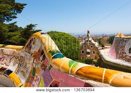 BARCELONA SPAIN - JUN 10 2014: Ceramic bench and buildings in the Park Guell designed by the famous architect Antoni Gaudi (1852-1926). UNESCO World Heritage Site