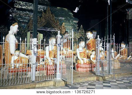 RANGOON / MYANMAR - CIRCA 1987:  Sculptures of the Buddha sit behind a metal picket fence at the Shwedagon Buddhist Pagoda in Rangoon.