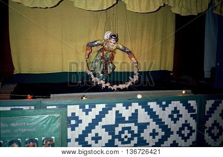 PAGAN, MYANMAR / CIRCA 1987: A puppet controlled by strings entertains people at a puppet show in Pagan.