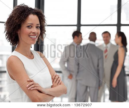 Potrait of a Young Beautiful Business woman smiling in from of Business team