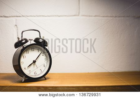 Alarm clock on table with blurred white brick background. Selective focus