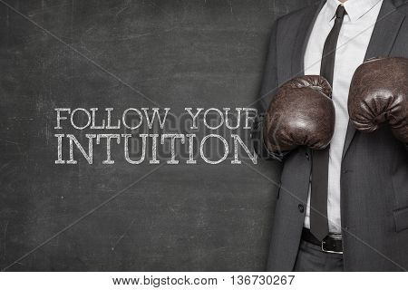 Follow your intuition on blackboard with businessman wearing boxing gloves