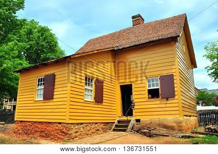 Old Salem North Carolina - April 21 2016: 1771 colonial wood frame Miksch House with stone foundation and single shutters *