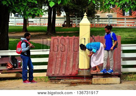 Old Salem North Carolina - April 21 2016: Three students check out an old-fashioned wooden water pump on Main Street -