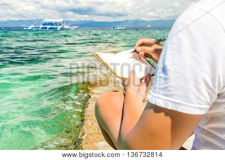 caucasian man is sitting on the breakwater of tropical turquoise sea and wrigting by pen in note pad at sunny summer day under cloudy sky
