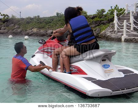 LAPU LAPU, CEBU / PHILIPPINES - JULY 28, 2011: People prepare for a ride in a jet ski at Shangri-La's Mactan Resort and Spa.