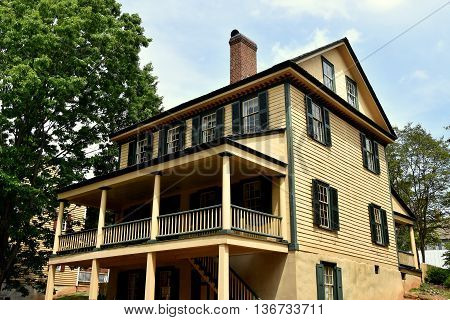 Old Salem North Carolina - April 21 2016: Expansive wood frame colonial home with exteriorstairway leading to front porch on Main Street
