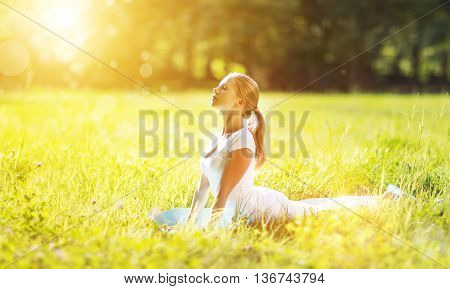 young woman enjoying fitness and yoga on green grass in the summer on nature