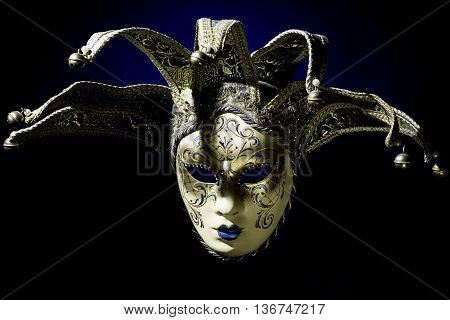 Venezian souvenir mask on black background with blue color poster