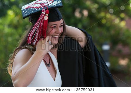 ATHENS, GA - MAY 2016: A smiling female graduate prepares to put on her graduation robe as she walks toward the graduation ceremony at the University of Georgia in Athens GA on May 13 2016.