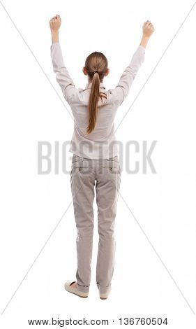 Back view of  business woman.  Raised his fist up in victory sign.    Raised his fist up in victory sign.Girl with long hair in a white jacket is raising his fists above his head.