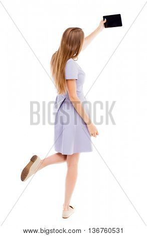 back view of standing young beautiful  woman  in vest and using a mobile phone. girl  watching. backside view of person.  Isolated over white background. girl in a blue dress makes self on the tablet