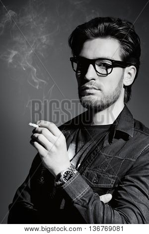 Black-and-white portrait of a smoking young man. Handsome young man thoughtfully and calmly smoking a cigarette. Men's beauty, fashion.
