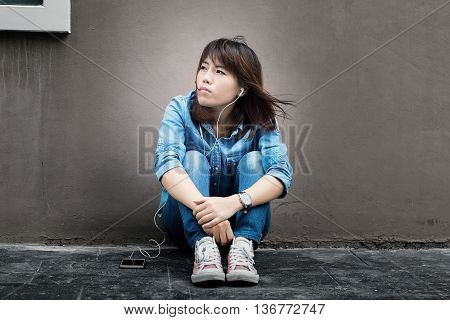 Asian woman sitting against a wall and listening to music