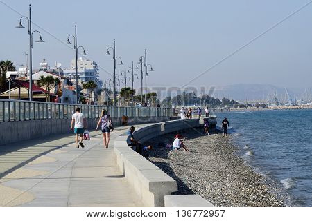 LARNACA CYPRUS - APRIL 7 2016: view of Larnaca seafront with palm trees pedestrians and beach on April 7 in Larnaca Cyprus.Larnaca - is a city on southern coast and capital of eponymous district.