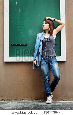 Asian woman standing against a wall and listening to music