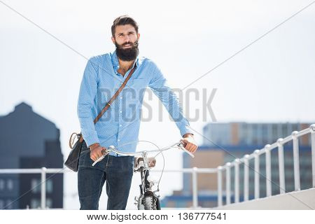 Hipster walking his bike in the city