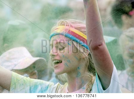 STOCKHOLM SWEDEN - MAY 22 2016: Smiling young blonde woman wearing bandeau covered with color powder in the Color Run Event in Sweden May 22 2016