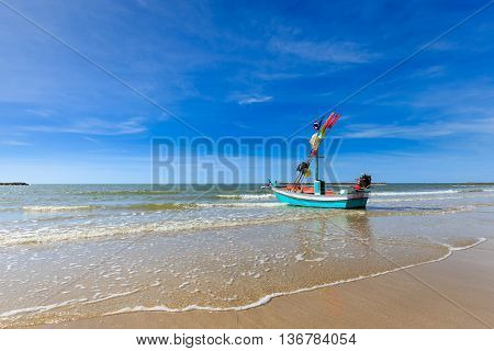 Small fishing boat on the beach with blue sky shallow fishing