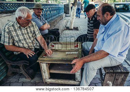 Borjomi Georgia - July 21 2015. Georgian men playing variety of backgammon game in Borjomi city