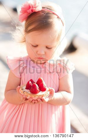 Cute baby girl 2-3 year old holding strawberry cake outdoors. Wearing stylish pink dress. Looking down. Childhood.
