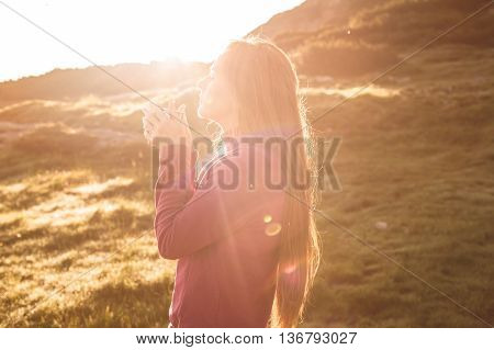 Young woman with long hair drinking tea at sunrise in mountains.