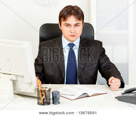 Dissatisfied modern business man banging fist on table