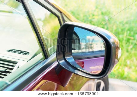 side rear-view mirror on a modern red car