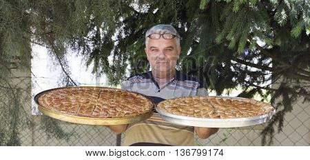 picture of a man holding two platters with fresh baked baklava