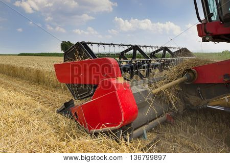 Combine harvester close up. Combine harvester harvesting wheat. Grain harvesting combine. Combine harvesting wheat. Wheat field blue sky. Close-up view of combine.