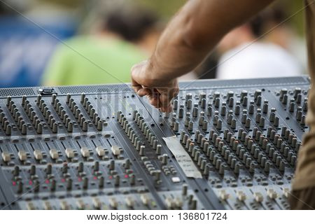 DJ adjusting audio mixer. Deejay hand over an audio mixing console.
