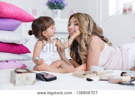 Cheerful young mother,blond with curly long hair and her little daughter,brunette, playing together on a white bed in a bright bedroom with mom's makeup kit, both dressed in white panties and white t-shirts