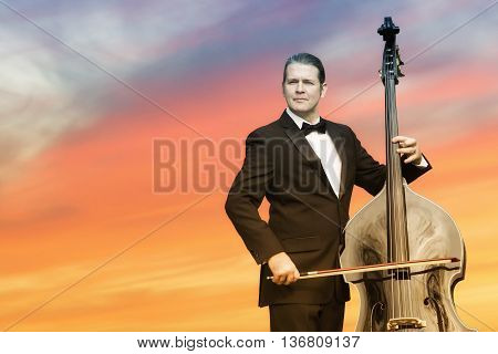 man in tuxedo playing the double bass in front of sunset