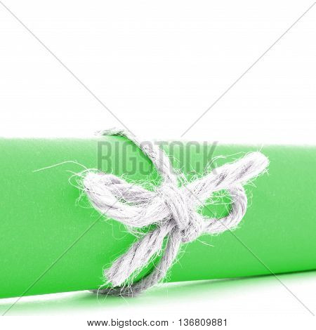 Handmade natural string bow tied on green paper scroll isolated