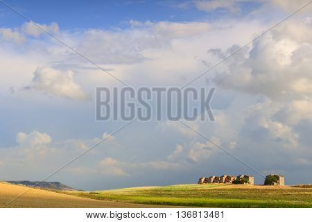 Between Apulia and Basilicata: farmhouses abandoned in a wheat fields.Italy. Summer: hilly rural landscape: farmhouses topped by clouds.