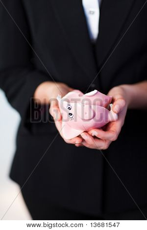 Young Business woman holding a broken piggy bank