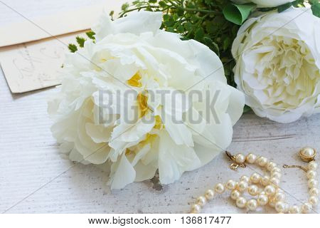 White fresh peony flowers posy with pearls jewellery close up on white wooden table poster