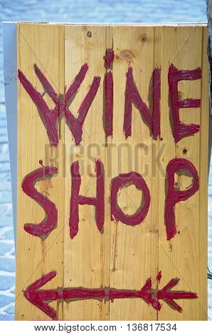 wooden sign indicating the presence of a wine shop
