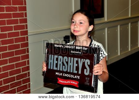 Hershey Pennsylvania - June 7 2015: A little girl holds up one of Hershey's world's largest candy bar at the Chocolate World super store