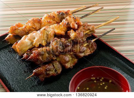 Food and Cuisine Chicken Grilled or Barbecue Chicken on Wooden Skewer Served with Spicy Sauce.