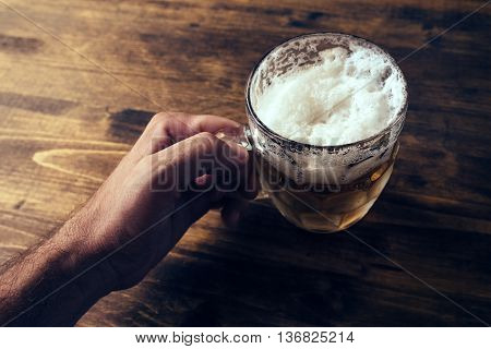 Hand holding beer mug full of cold fresh alcohol drink on wooden background man in the bar pov shot selective focus