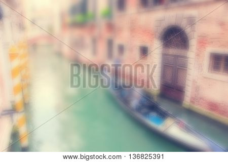 Defocused Background with Gondola with Tourists and a Gondolier in a narrow water canal between old buildings in Venice Italy.