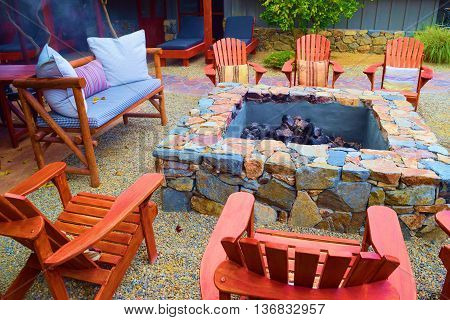 Rustic wooden chairs surrounding an outdoor fire pit in a residential backyard